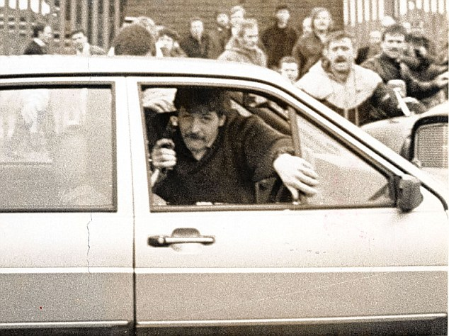 Desperation: Corporal Wood, with a gun in his hand, is pictured moments before he was dragged from his car by members of the crowd