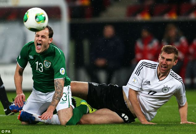 Painful: Anthony Stokes is fouled by Germany's Per Mertesacker (right)