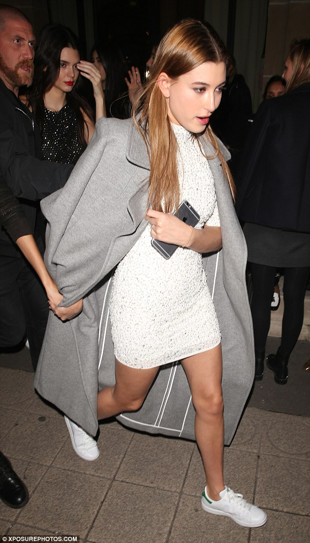 Keeping warm: Hailey layered a long grey coat over her skimpy dress and followed Kendall's lead by wearing white trainers