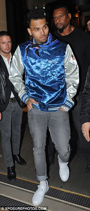 Looking dapper: The singer layered a navy blue jumper and his statement jacket