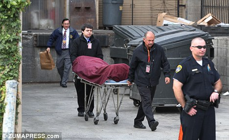 Death: The body of Alfonso de Bourbon is removed after being found crushed between a series of three dumpsters and the loading dock wall at Jonathan's market