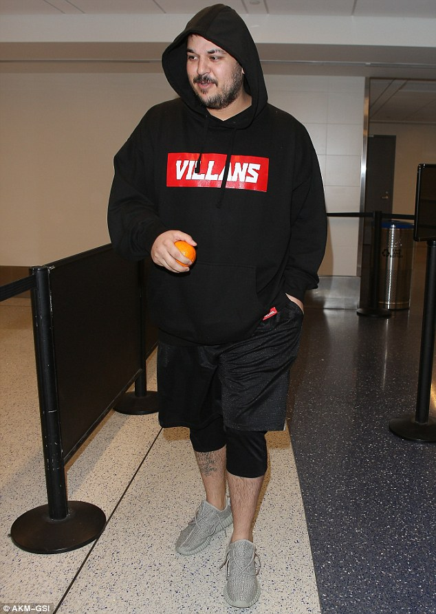 Slimmed down: Rob Kardashian showed off his weight loss as he arrived at LAX to catch a flight on Monday