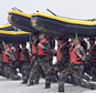 FILE - In this May 14, 2009 file photo, Navy SEAL trainees carry inflatable boats at the Naval Amphibious Base Coronado in Coronado, Calif. Navy SEAL teams don¿t have enough combat rifles to go around even as these secretive, highly trained forces are relied on more than ever to hunt down members of the Islamic State group and other terrorists, according to SEALs who have confided in Rep. Duncan Hunter, R-Calif. (AP Photo/Denis Poroy, File)