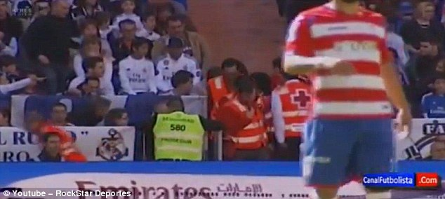 Stewards and fans rush to the attention of Casillas following the incident at the Santiago Bernabeu
