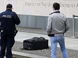 Police officers photograph a suitcase in front of the US embassy in Berlin, Germany, Friday, March 11, 2016. A 23-year-old German man is in custody after falsely claiming to have a bomb inside a suitcase he was trying to bring into the U.S. Embassy, police said Friday. (AP Photo/Ferdinand Ostrop)
