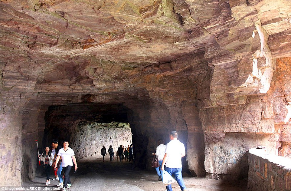 Tourists take in the spectacular views of the canyon through one of the road's 'windows' that were originally carved out to remove loose debris