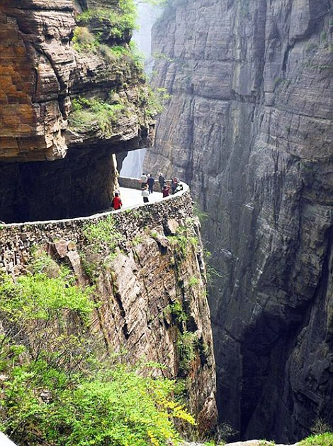 The road is carved out of the cliff-side