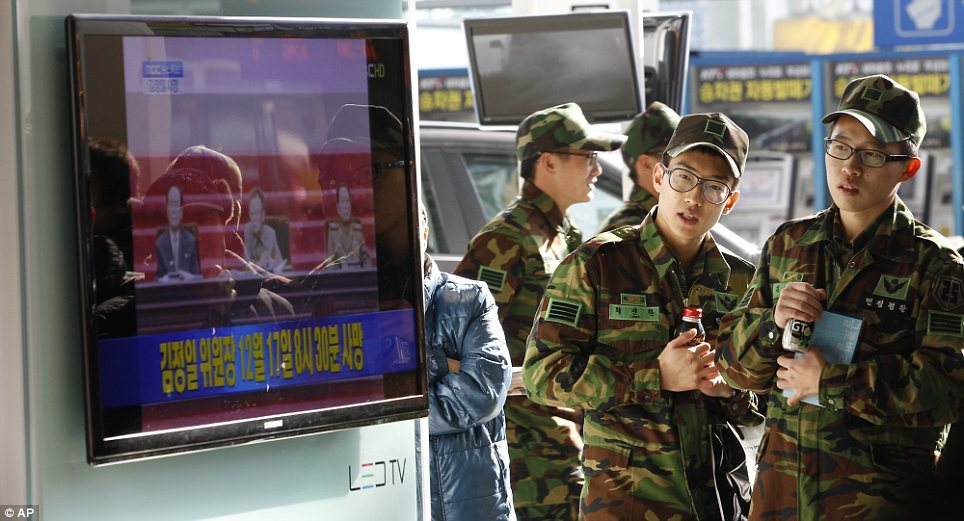Surprise: South Korean soldiers react as they watch a news broadcast reporting the death of North Korean leader Kim Jong Il at the Seoul train station in Seoul, South Korea
