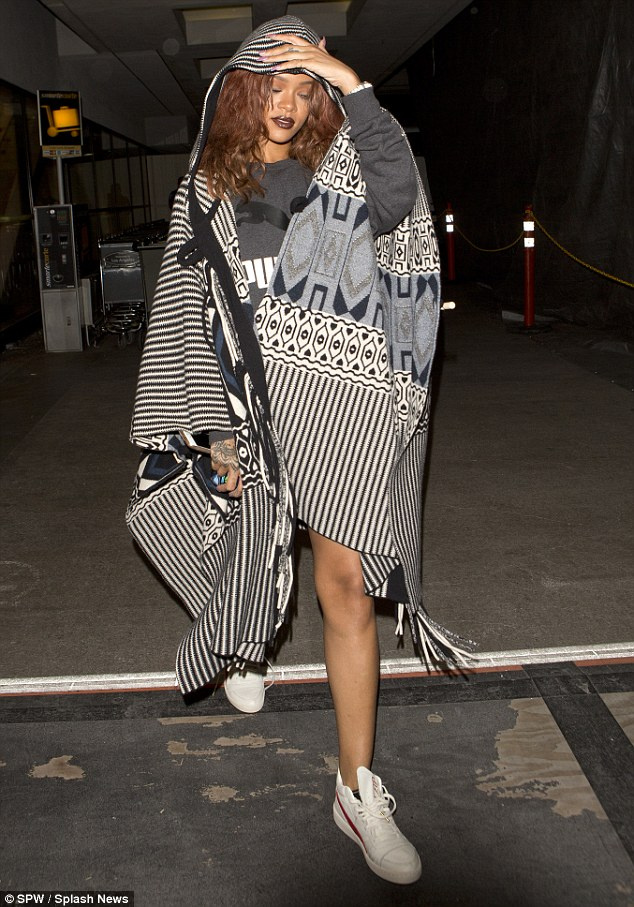 Don't mind me: Rihanna appeared keen to keep a low profile, despite her ensemble suggesting otherwise