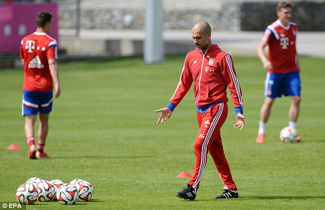 Guardiola heads towards the balls during the training session at the club's base in Munich