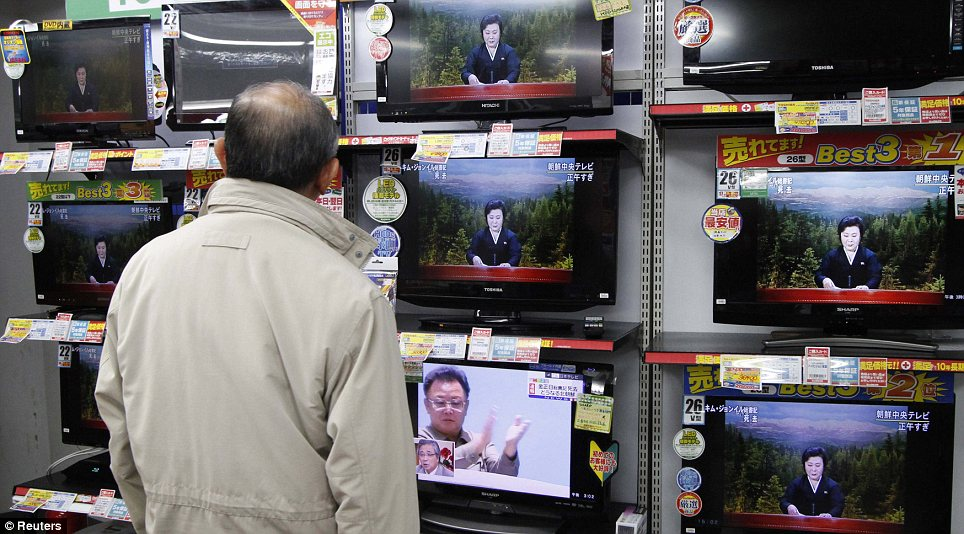 Coverage: A man watches the reporting of the death of Kim Jong Il on an electronics store in Tokyo, Japan