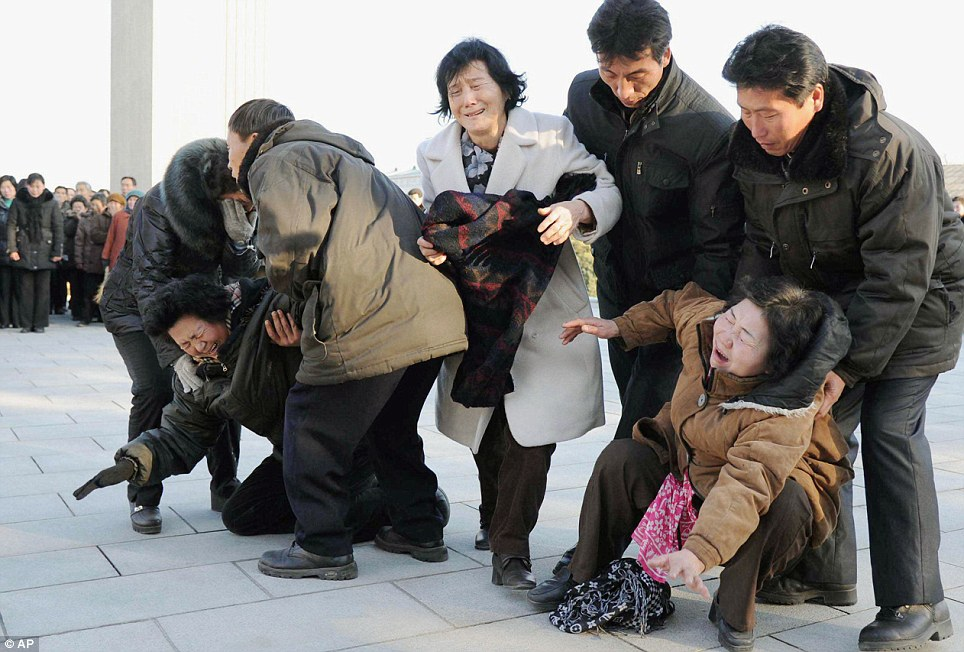 Too much to take: Women collapse in tears in the streets of Pyongyang as the nation mourned the passing of Kim Jong Il