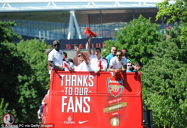 Bringing up the rear: Arsenal players stand at the back of the bus with the Emirates in the distance