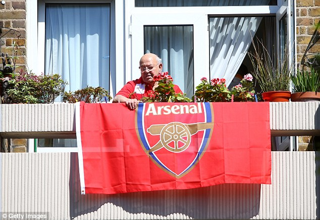 Suitable for all ages: An elderly Arsenal fans watches the procession from the comfort of his balcony