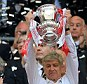Silver service: Manager Arsene Wenger pictured lifting the FA Cup much to the delight of his Arsenal players