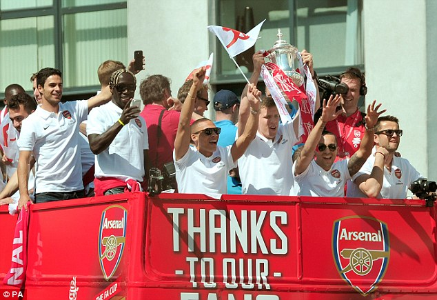 The wait is over! Arsenal players celebrate breaking their trophy drought by raising the FA Cup