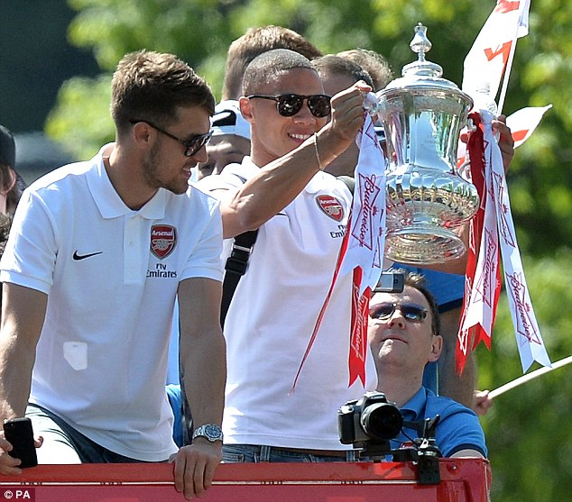 Riding shotgun: Aaron Ramsey (L) and Kieran Gibbs (R) were at the front of the bus to show off the trophy
