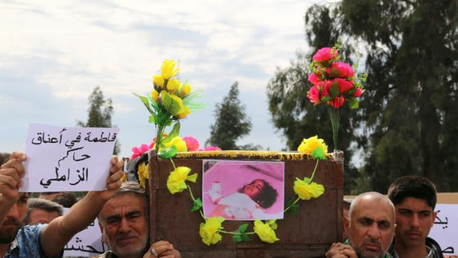 Iraqis carry the coffin of a young girl who was killed following a chemical attack on Taza, a town on the outskirts of Kirkuk, on March 11, 2016