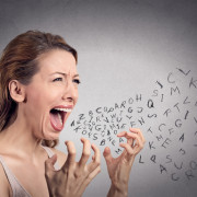 Side view portrait angry woman screaming, alphabet letters coming out of open mouth, isolated grey wall background. Negative human face expressions, emotion, reaction. Conflict, confrontation concept