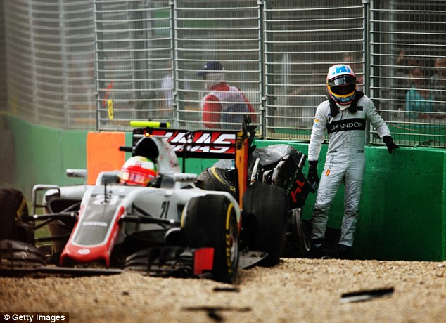 Alonso climbs out of his McLaren and watches on with shock asGutierrez remains seated in his Haas car