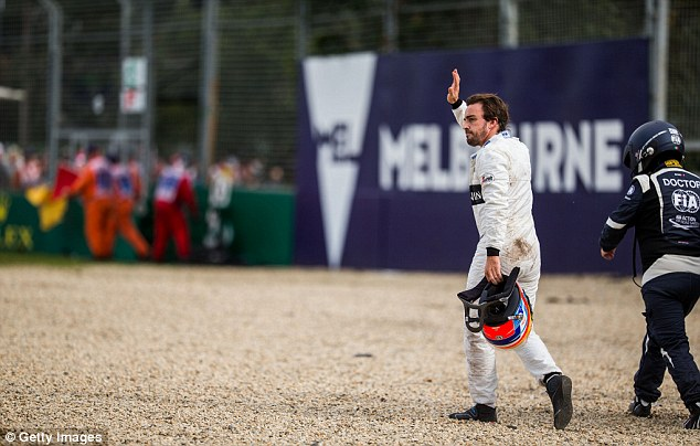 The 34-year-old Spaniard acknowledges the crowd while he is applauded for climbing out of his wrecked car