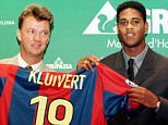 Barcelona's new Dutch soccer star Patrick Kluivert (R) holds his shirt helped by his compatriot coach Louis van Gaal during a presentation ceremony at Barcelona's stadium September 1. Kluivert signed a four-year contract with the Spanish league champions FC Barcelona. - RTXI26Z
