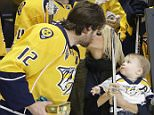 Nashville Predators forward Mike Fisher kisses his wife, singer Carrie Underwood, as Fisher is honored for his 1,000th NHL hockey game before the first period of a game against the Los Angeles Kings Monday, March 21, 2016, in Nashville, Tenn. Underwood holds their son, Isaiah. (AP Photo/Mark Humphrey)