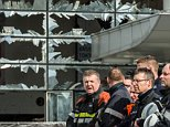 Firefighters and first responders stand next to blown out windows at Zaventem Airport in Brussels on Wednesday, March 23, 2016. Belgian authorities were searching Wednesday for a top suspect in the country's deadliest attacks in decades, as the European Union's capital awoke under guard and with limited public transport after scores were killed and injured in bombings on the Brussels airport and a subway station. (AP Photo/Geert Vanden Wijngaert, Pool)
