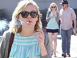 **EXCLUSIVE**  Date: March 26th 2016   Photo Credit: MOVI Inc.\nActress Kirsten Dunst shows off her long legs in a pair of short black hot pants as she enjoys a cosy cigarette and a ugh with a mystery male companion after breakfast in Studio City,CA.