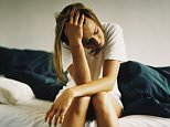 A stock photo of a woman suffering from a severe depression.     Young woman sitting on edge of bed, holding head in hand