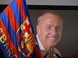 """A FC Barcelona's supporter holds a FC Barcelona flag offering his respects as a photograph is displayed showing the late Dutch soccer Johan Cruyff at the Camp Nou stadium in Barcelona, Spain, Tuesday, March 29, 2016. Dutch soccer great Johan Cruyff, who revolutionized the game as the personification of """"Total Football,"""" has died. He was 68. (AP Photo/Manu Fernandez)"""