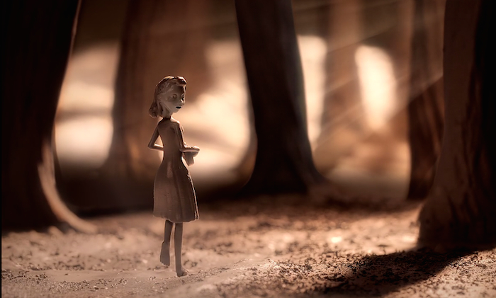 The main character from Chase me - a slender girl with mid-length hair - looks over her shoulder as she walks through the woods.