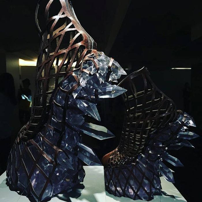 A pair of 3d-printed shoes designed by Iris van Herpen. A mesh seemingly made out of leather encases the foot area, while the dramatic heel and platform is adorned with large, fierce-looking crystals sticking out from the shoe.