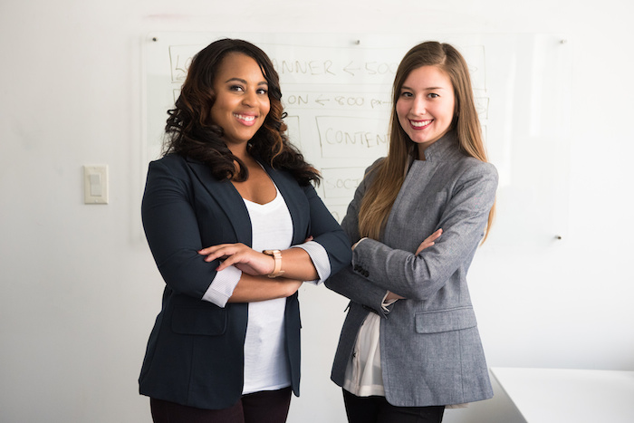 Two women from the #WOCinTech photoshoot standing in front of a whiteboard, arms crossed and smiling at the camera.