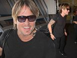 Keith Urban at Sydney Airport poses with a fan for pictures.\nEXCLUSIVE\n30 March 2016\n©MEDIA-MODE.COM