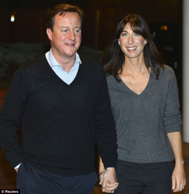 Wrapped up: David Cameron, pictured wearing a jumper with wife Samantha, would encourage people to consider people to wear an extra layer during the cold weather