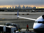 FILE - In a May 1, 2015 file photo, a United Airlines employee walks near a jet parked at Terminal C of Newark Liberty International Airport as the sun rises behind the New York City skyline, in Newark, N.J. The Federal Aviation Administration announced Friday, April 1, 2016, that it is easing limits on the number of hourly flights at Newark Liberty International Airport, and the airport¿s operator said that should lead to greater competition and lower fares.(AP Photo/Julio Cortez, File)