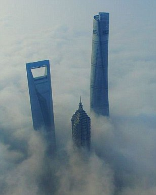 Only the tops of the Pudong skyscrapers were visible emerging from the thick fog, which was caused by high levels of humidity in the city