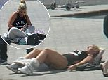 PLEASE NOTE EMBARGO - NO ONLINE USE UNTIL 00.01 GMT/BST 4/4/2016. Kerry Katona in  in the Canary Islands. See SWNS copy SWKERRY: Kerry Katona lies sprawled across an airport car park with her jogging bottoms around her ankles. It is 11 in the morning and the reality TV star looks totally unreal. Kerry, 35, seems unaware of shocked holidaymakers as a friend pulls her trousers up and shepherds her into the terminal at Gran Canaria airport. The shocking footage, captured by another passenger, will spark fears that she is back in the grip of booze. The mum of five was diagnosed as an alcoholic after a stint in The Priory. Our exclusive pictures show Kerry on the day she arrived in the Canary Islands after boarding a 7am flight from Gatwick airport near London. Before take-off, she tweeted a picture to her 469,000 Twitter followers of herself holding a full champagne flute.