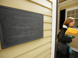 A passer-by walks near a newly unveiled plaque attached to Wadsworth House, Wednesday, April 6, 2016, on the campus of Harvard University that honors four slaves that had been owned by and worked for Harvard's past presidents, in Cambridge, Mass. (AP Photo/Steven Senne)