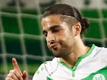 Wolfsburg's Swiss defender Ricardo Rodriguez (L) celebrates scoring from the penalty spot past Real Madrid's Costa Rican goalkeeper Keylor Navas (R) with his team-mates during the UEFA Champions League quarter-final, first-leg football match between VfL Wolfsburg and Real Madrid on April 6, 2016 in Wolfsburg, northern Germany.  / AFP PHOTO / ODD ANDERSENODD ANDERSEN/AFP/Getty Images
