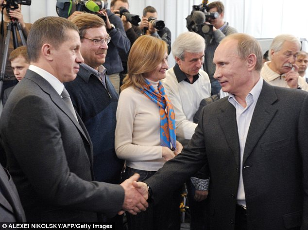 Prime minister Vladimir Putin shakes hands with his staff and supporters among the United Russia ruling party's campaigners