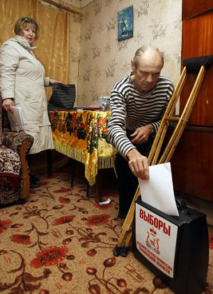 Yuri Zaitsev votes at his home in the village of Oster, 237 miles west of Moscow, as an election commission official looks on, left