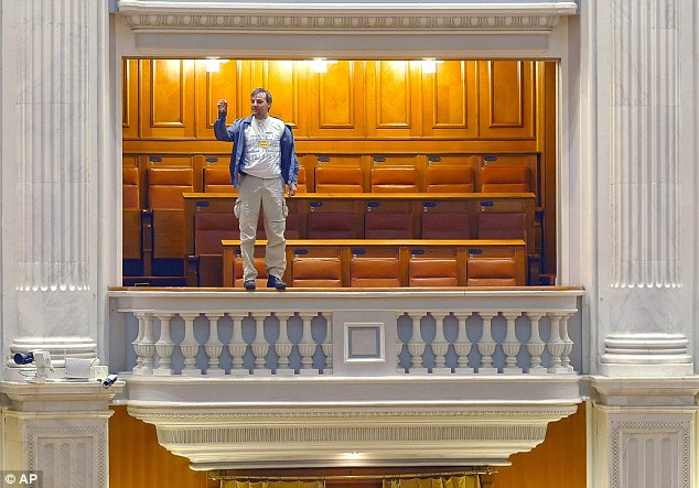 Adrian Sobaru, an electrician at the national television station, gestured as he stood on the handrail of a balcony at Romania's Parliament