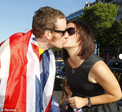 A kiss for the victor: Bradley Wiggins is greeted by his wife Catherine after emerging triumphant from the final stage of the Tour de France