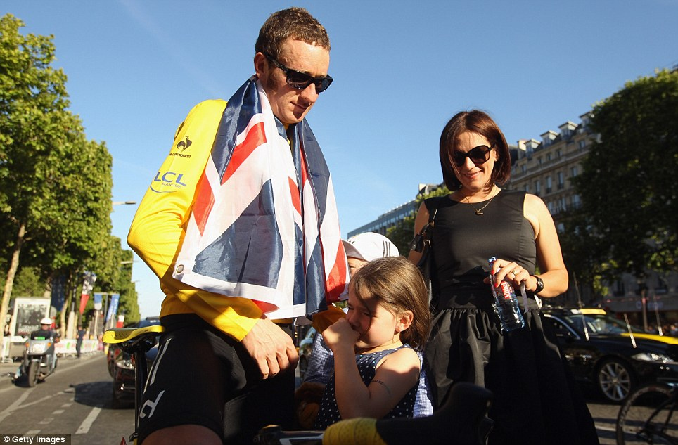 Bored: Isabella Wiggins, flanked by dad Bradley and mum Catherine, looks less than impressed as her father celebrates