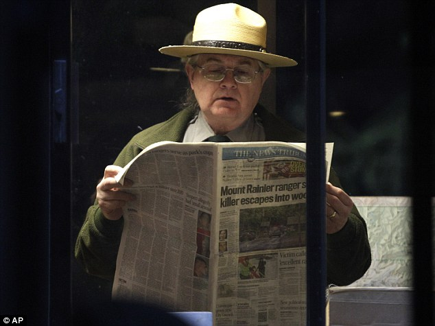 Loss: Park Ranger Ralph Davis reading a copy of the Tacoma News Tribune after his colleague Margaret Anderson was shot dead