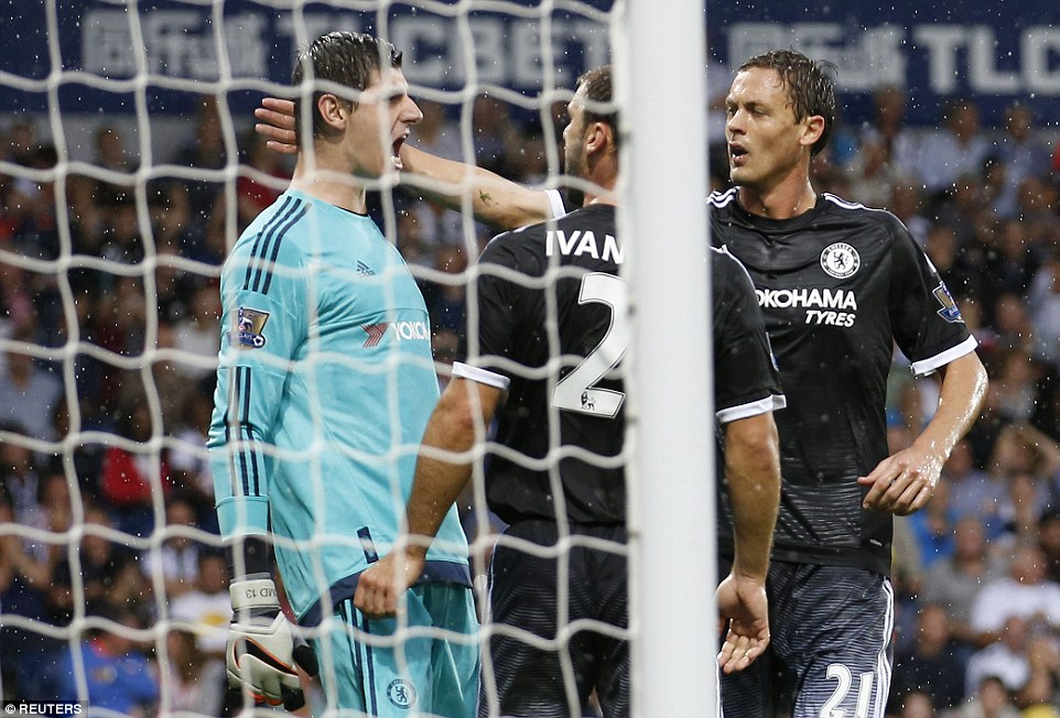 Chelsea goalkeeper Courtois is swamped by his team-mates after saving Morrison's penalty, which Chris Brunt wanted to take