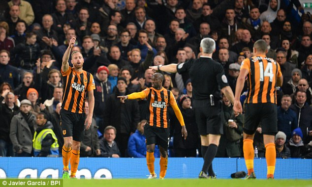 Chris Foy (second right) points for a goal kick and wrongly failed to produce a second yellow for Cahill