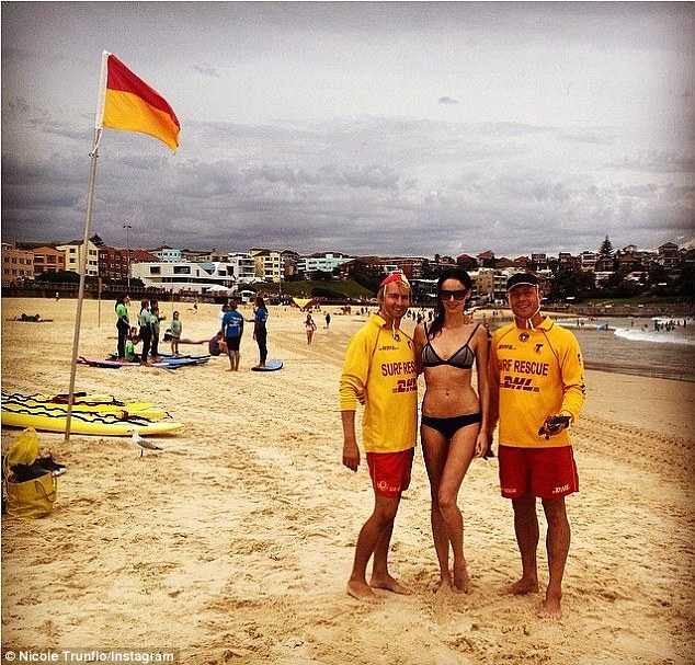 Ominous sky: Nicole celebrated her 28th birthday at Bondi beach on Sunday, posing with two lifeguards
